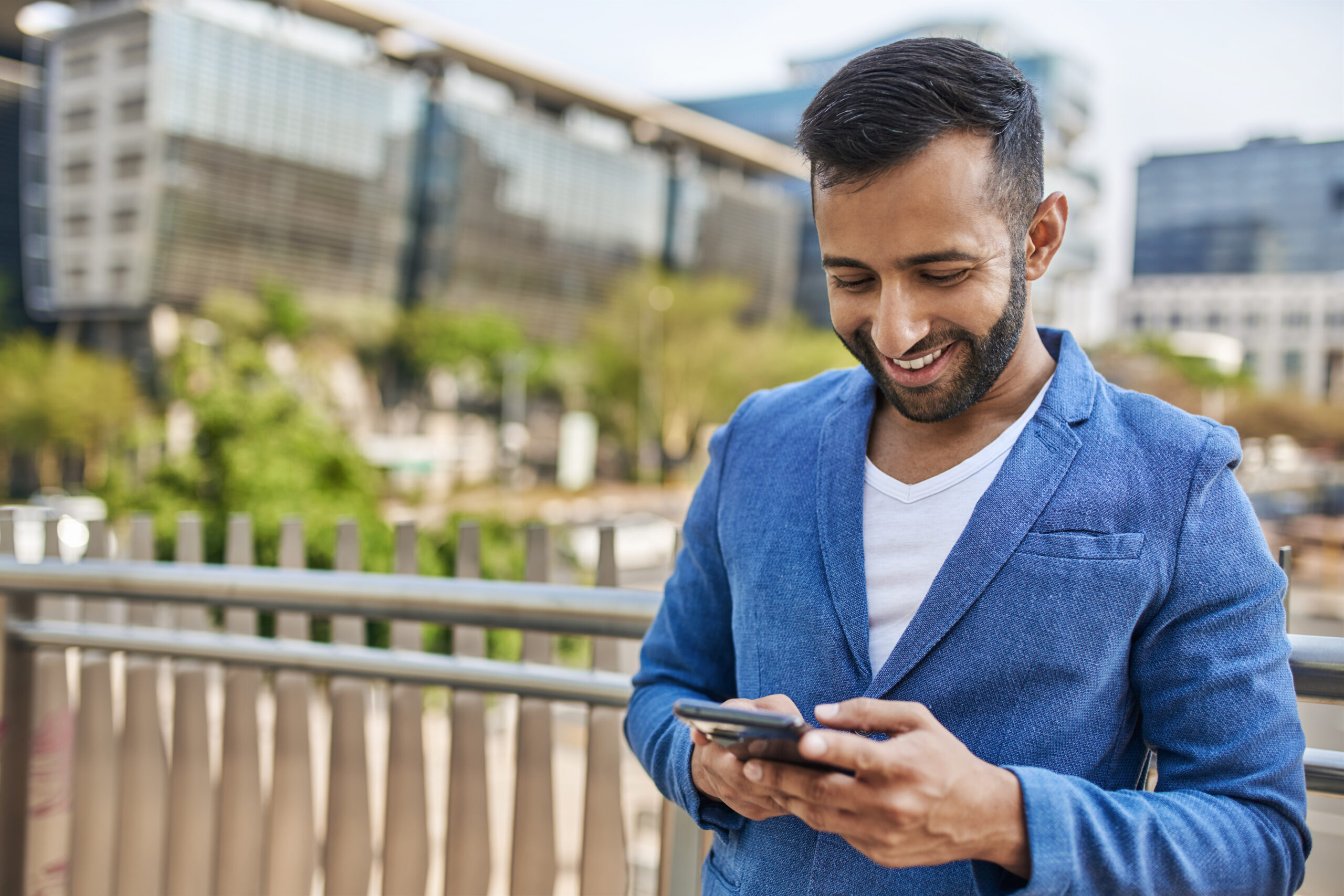 Young attractive smiling bearded indian Arabic businessman typing on mobile phone with city buildings in the background and copy space