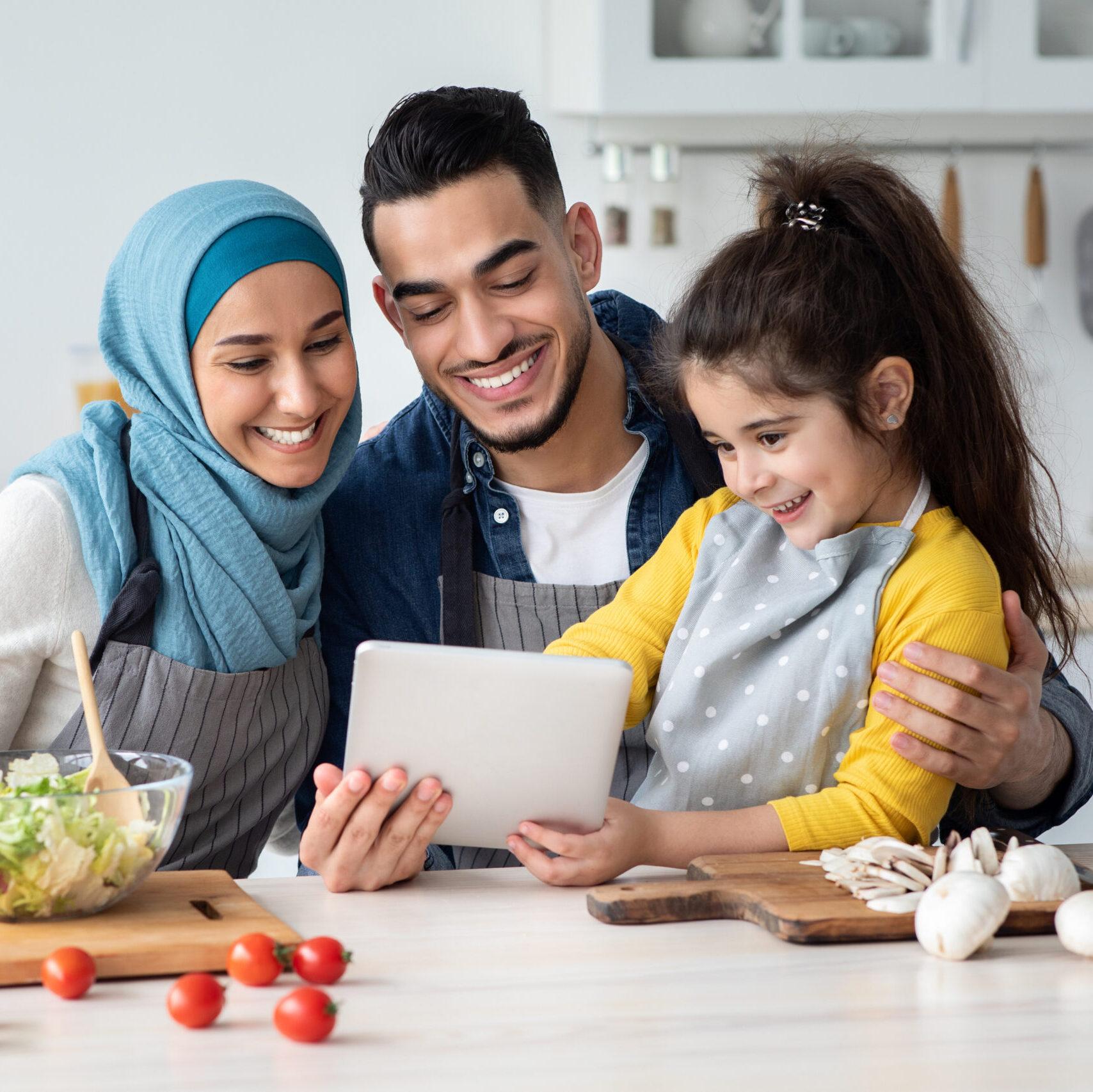 Happy Muslim Family Using Digital Tablet While Cooking In Kitchen Together, Cute Little Arab Girl And Her Islamic Parents Checking Online Recipe On Tab Computer While Preparing Food At Home